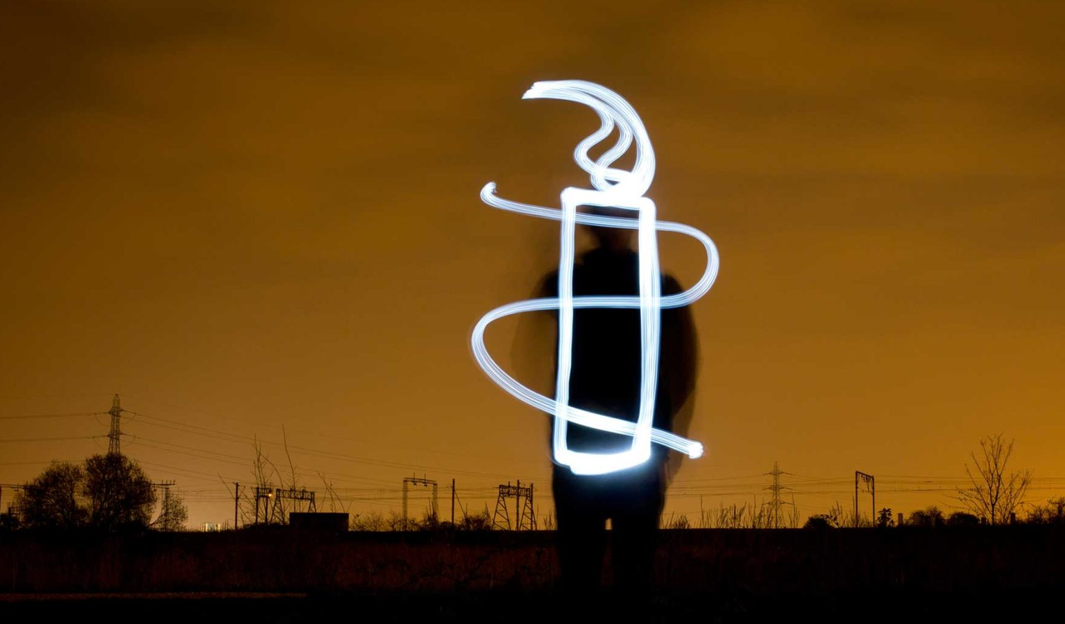 A light artist stands against a dark night sky and paints the AI candle.