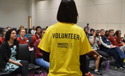 Person in a yellow amnesty volunteer tshirt stands in front of a crowd of seated people