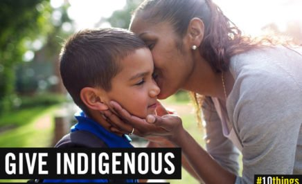 Indigenous woman kissing young Indigenous boy on the cheek
