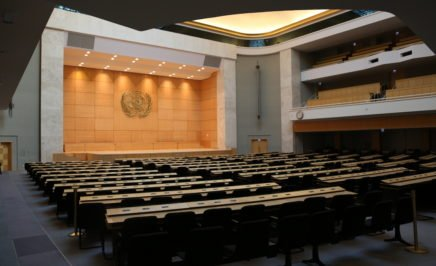Interior photograph of the large international meeting chamber room at the UN in Geneva, Switzerland. The room is empty.