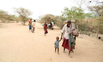 A man walks with a young boy carrying their possessions in Dadaab Refugee camp - Kenya
