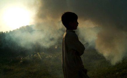 A young boy walks through clouds of smoke at the Sheikh Shehzad camp