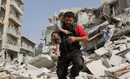 A man and his child behind a bombed building