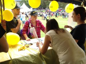 Volunteers stand behind an Amnesty International Stall at Mardi Gras - the table is decorated with yellow table-cloth, and yellow balloons hang above. The volunteers are pictured speaking to interested people about a campaign.