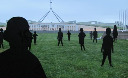 Cardboard silhouettes of children on the lawn outside parliament house