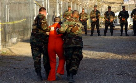 Guantanamo Camp X-Ray. U.S. Army Military Police escort a detainee to his cell in Camp X-Ray at Naval Base Guantanamo Bay, Cuba.
