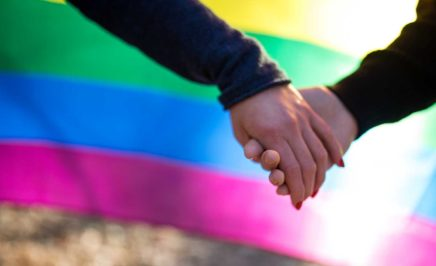 Two people holding hands in font of a rainbow flag
