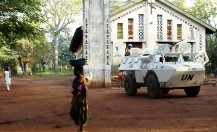 A woman passes in the foreground, a UN armoured vehicle stands in front of a church
