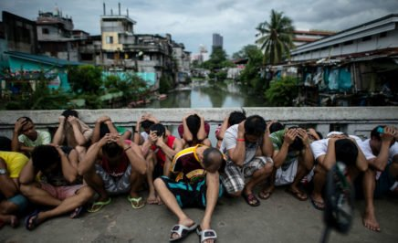 Drug suspects in the Philippines sit on the ground with their heads down, a canal and city skyline in the background