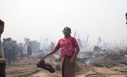 A Rohingya woman grieves after a fire gutted her family's shelter, Rakhine state, May 2016