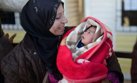 Syrian refugee woman holds her baby.