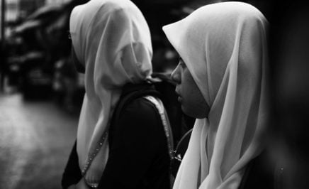 Two women wearing head scarves.