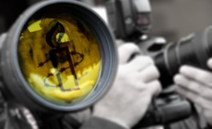 This is an image of a camera lens with a yellow Amnesty candle reflected in it. It was created as a youtube header image.