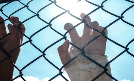 A child's hands on a fence
