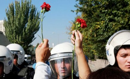 People hold carnations in front of riot police during clashes in Turkey