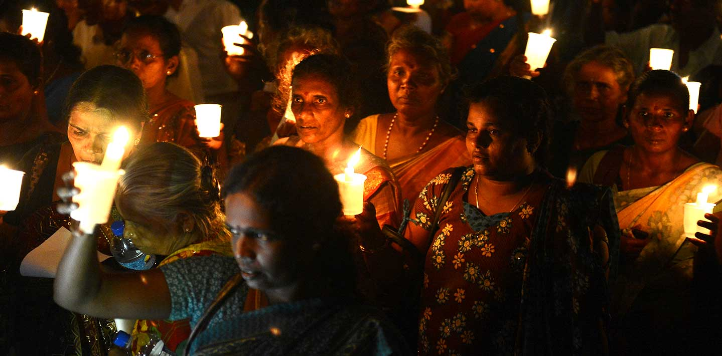 Sri Lankan activists hold lighted candles during a candlelight vigil in Colombo