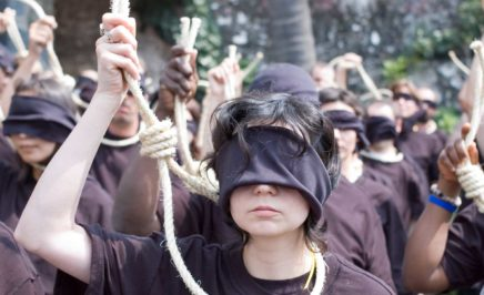 Amnesty protester wear blindfolds and hold a noose