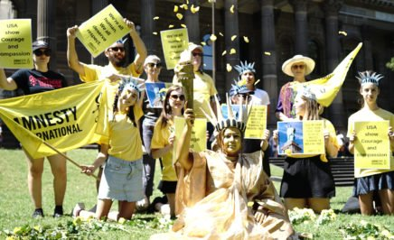 Half a dozen Amnesty supporters on a lawn, dressed in yellow and waving an Amnesty flag. One person is wearing a gold statue of liberty costume.