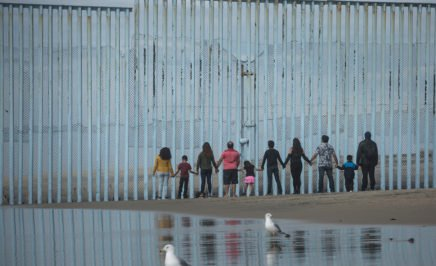People facing a wall on the Mexico Border