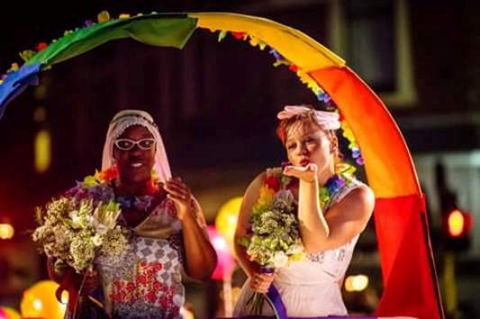 Image from Pride Rally Perth 2017. Two brides holding hands, standing under a rainbow arch. One bride is blowing a kiss to the crowd while the other holds a bouquet.
