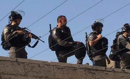 Armed guards stand on top of a wall.