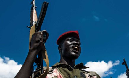A Sudan People's Liberation Army (SPLA) soldier holds up a gun