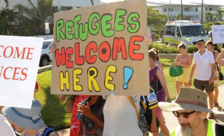 Homemade banner from the Palm Sunday refugee rally in Townsville. Colourful cardboard banner states 'Refugees welcome here'.