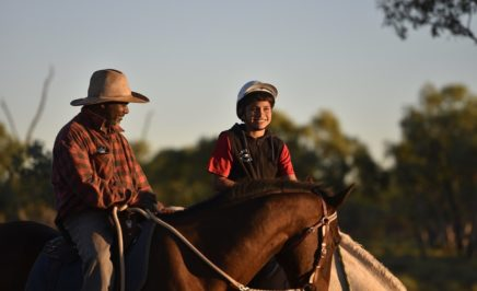 A young boy rides a horse with an Indigenous elder