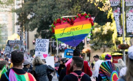 A photo of a crowd of people gather for a rally marriage equality rally in Sydney. There are numerous people holding rainbow flags and carrying signs that say 'Love!' and 'Vote Yes!'