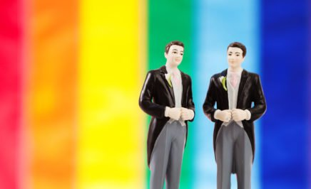 Two groom figures on a wedding cake in front of a pride flag. © iStock/YinYang
