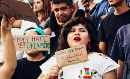 A close up photograph of protesters at a rally against ending the Deferred Action for Childhood Arrivals (DACA) programme in Los Angeles in 2017. The image shows a young women standing at the front of the crowd holding a sign that says 'United We Dream, #DefendDACA, equality'. Another sign, held up by a young man says 'Deport hate, not Dreamers'. In the background of the image is a young girl on her father's shoulders staring straight at the camera.