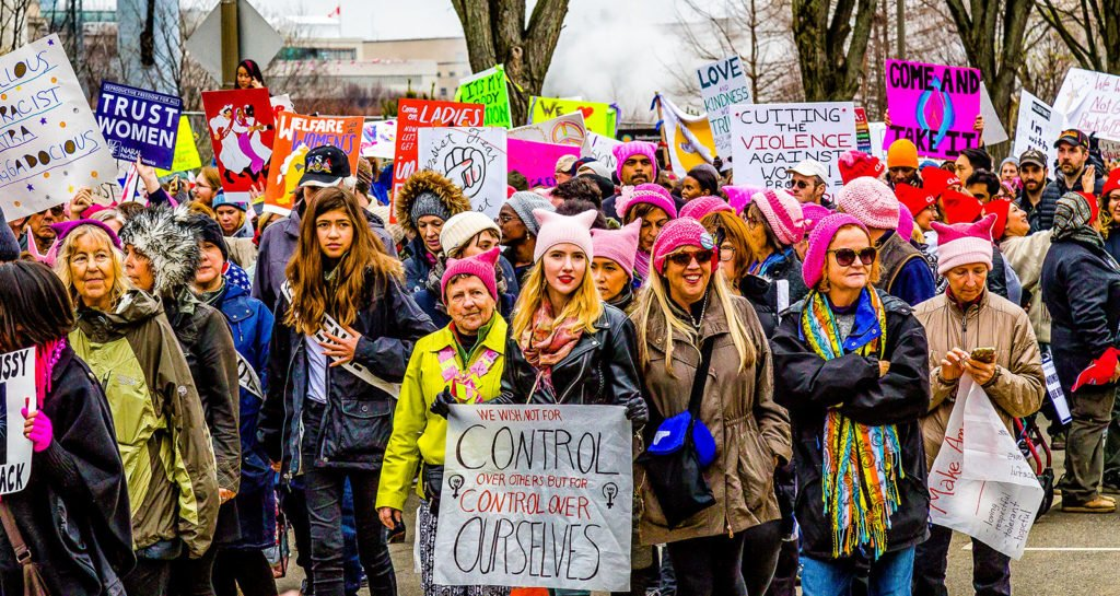 A close up photograph of people taking part in the Women's March on Washington DC on 21 January 2017. The image shows a mixed crowd of men and women holding placards and marching, some of whom are wearing pink hats. A young woman at the front of the shot holds a sign that says 'We wish not for control over others but for control over ourselves.'