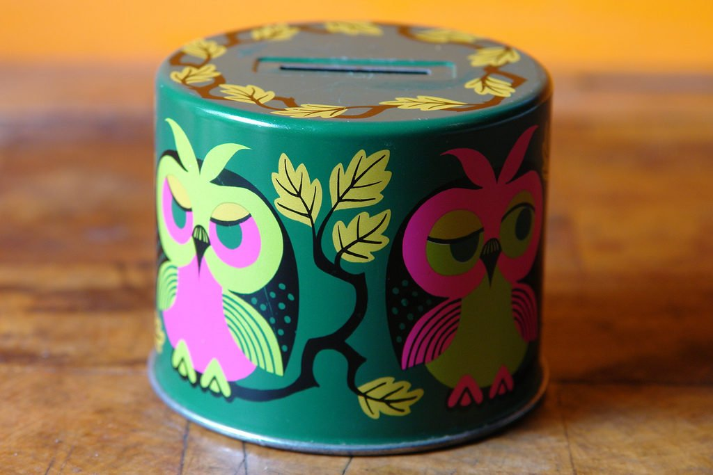 A round money box painted green, with painted florals and owls on it.