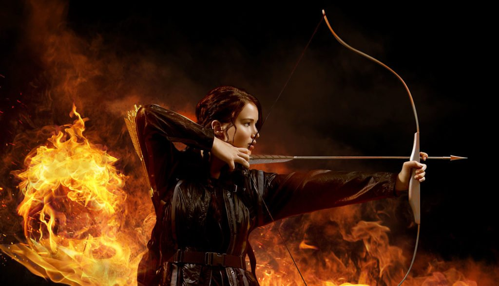 A still from the movie 'The Hunger Games'. The image shows Jennifer Lawrence as Katniss Everdeen, firing an arrow into the distance, flames in the background.