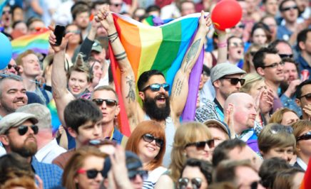 A man holding a rainbow flag at a rally. © EPA