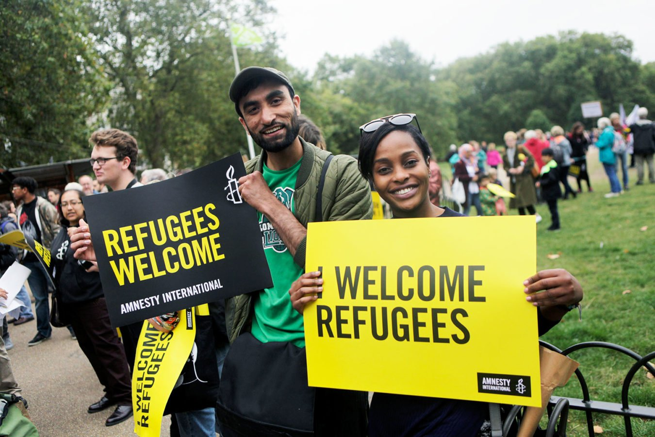 A man and woman at a rally in London to welcome refugees. They smile into the camera holding signs bearing the Amnesty International logo that say 'Refugees welcome'.