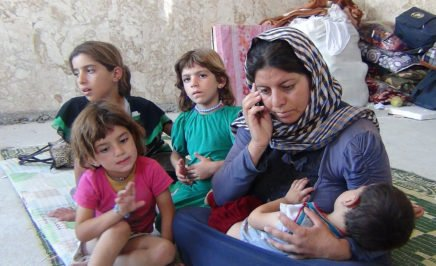 A photo a woman and her children at an IDP camp in Northern Iraw. Sawsan Hassan is trying to contact her husband, who was abducted by IS on 3 August 2014, by mobile phone.