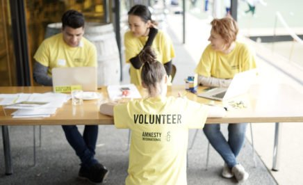Four Amnesty volunteers, three are sitting at a table filled with member sign-up forms and a fourth volunteer is standing in front of them with her back to the camera. She is wearing an Amnesty tshirt with the word 'Volunteer' emblazoned across the back.