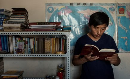 young man reading a book and standing next to a bookcase