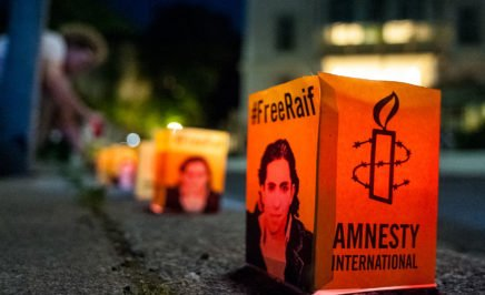 A row of paper candles with Raif Badawi's image printed on the side and the Amnesty International logo