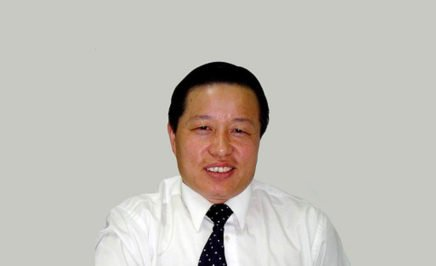 Human rights lawyer Gao Zhisheng smiling into the camera. He is wearing a black tie and white shirt and the background behind him is a grey wall.
