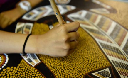 Close up photo of the arm of a young woman as she works on an Aboriginal painting.
