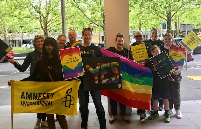 Canberra activists holding rainbow flags and banners at a Marriage Equality Rally in Canberra
