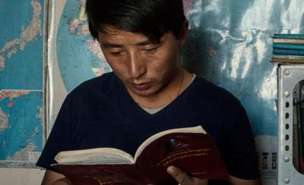 Tashi Wangchuk reading Tibetan text in front of world map