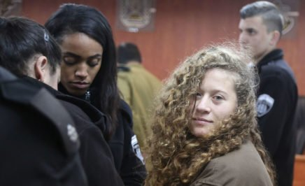 A young woman with curly hair and wearing a brown jacket stands in a court room surrounded by guards. She is looking at the camera.