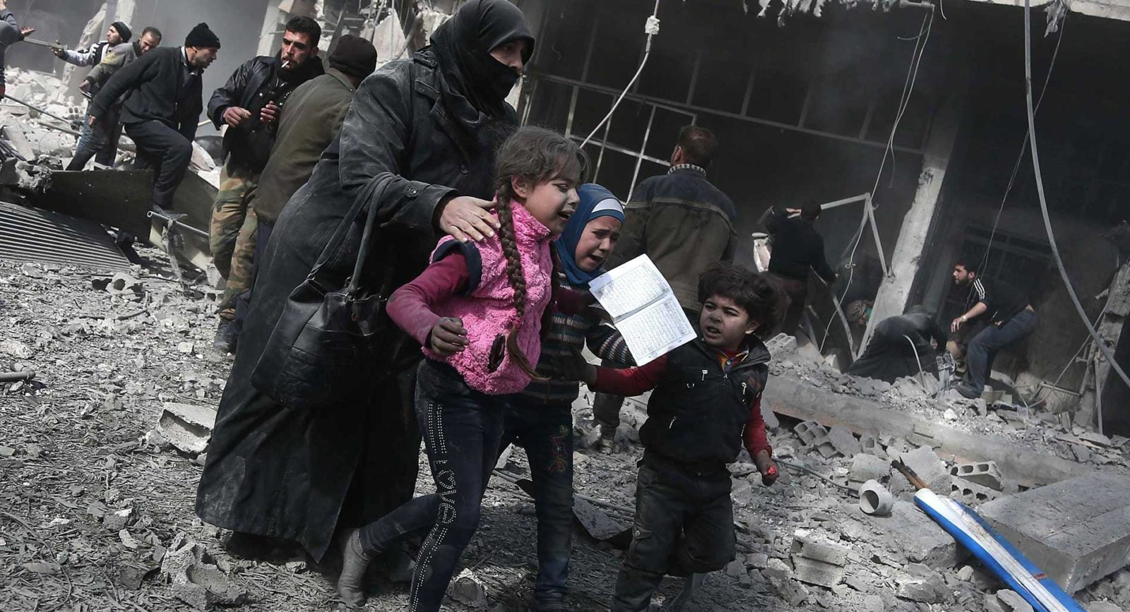 A Syrian woman and children run for cover amid the rubble
