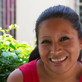 Portrait photo of Teodora Vasquez, jailed for ten years in El Salvador for having a miscarriage. She is in the prison, smiling towards the camera.,