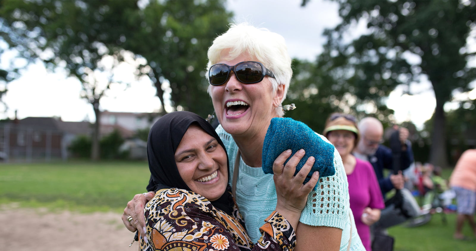 Woman in with head scarf hugs a laughing, middle-aged woman of Western appearance.
