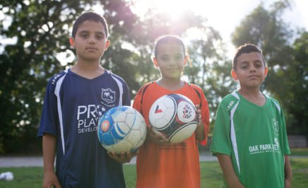 Three children holding soccer balls and wearing soccer jerseys in a sunlit park.