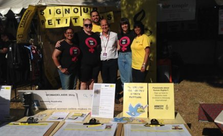 Amnesty's women's rights activists stand in front of a stall at WOMAD